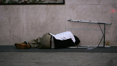A homeless man sleeps on a Skid Row sidewalk in Los Angeles, Calif. on Oct. 12, 2007. Photo by David McNew/Getty Images